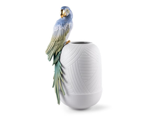 Colourful Macaw bird perches on the side of the white vase